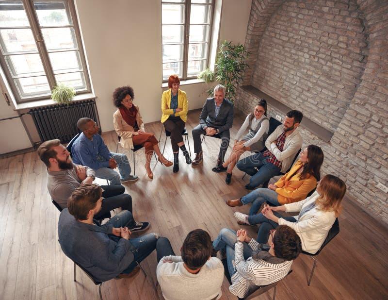 Executivos que sentam-se no círculo na sala de direção e que discutem imagem de stock royalty free