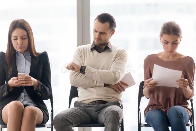 Executivos que sentam-se no encontro de espera da fileira a começar foto de stock royalty free