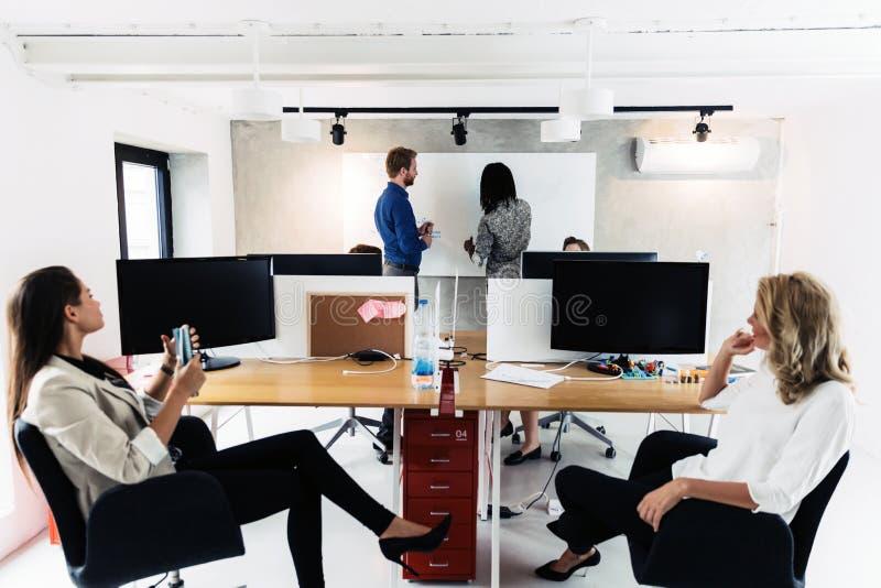 Executivos que sentam-se no escritório e que aprendem novas tecnologias imagem de stock
