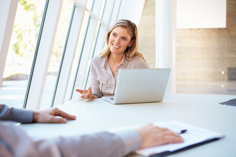 Executivos que têm a reunião em torno da tabela no escritório moderno imagens de stock
