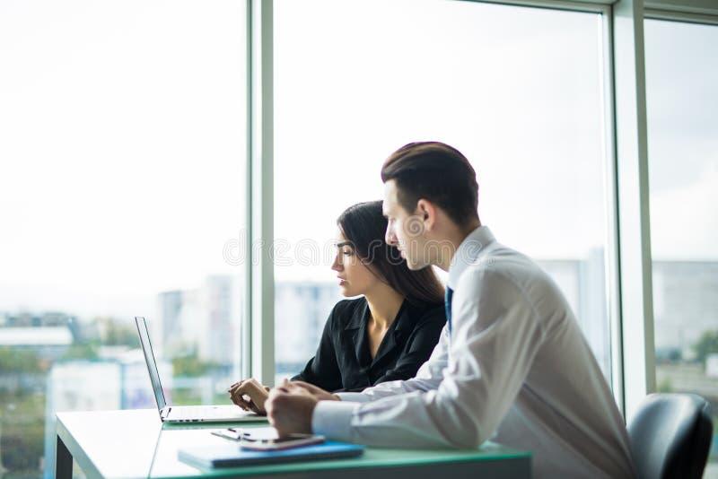 Executivos que têm a reunião em torno da tabela no escritório moderno contra janelas foto de stock royalty free