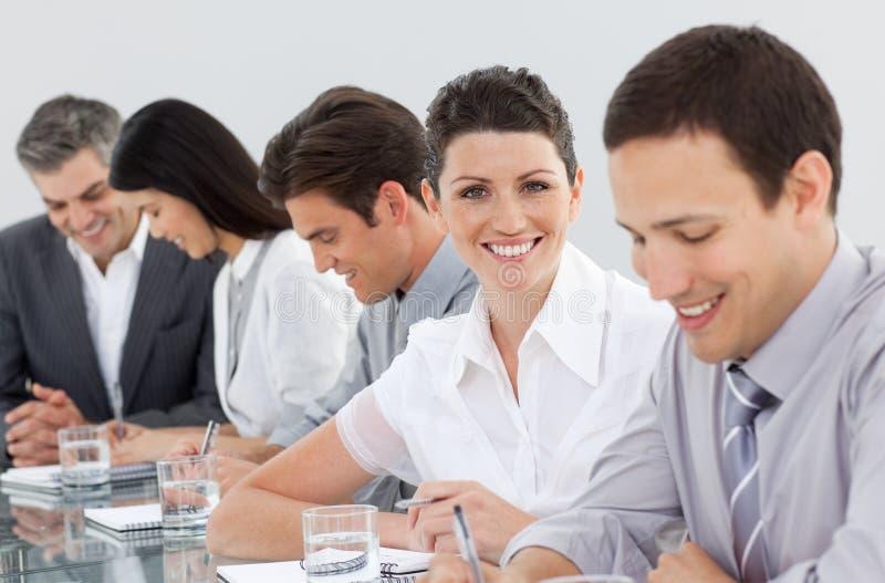 Executivos que tomam notas em uma reunião imagem de stock