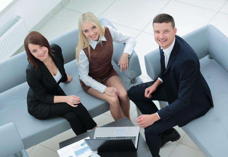 Executivos que trabalham em torno da tabela no escritório moderno fotografia de stock royalty free