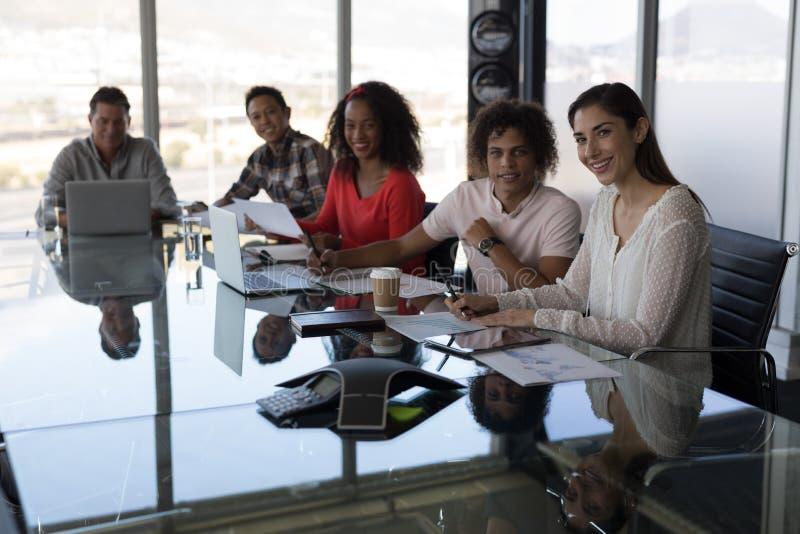 Executivos que trabalham na tabela e que olham a câmera no escritório fotos de stock royalty free