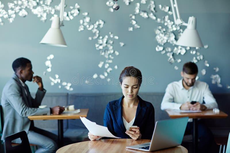 Executivos que trabalham no interior moderno do café fotografia de stock