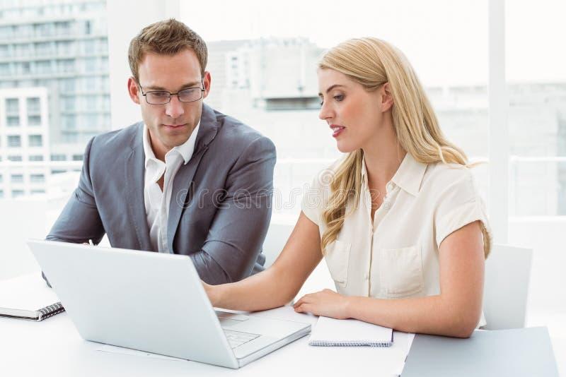 Executivos que usam o portátil no escritório fotos de stock royalty free
