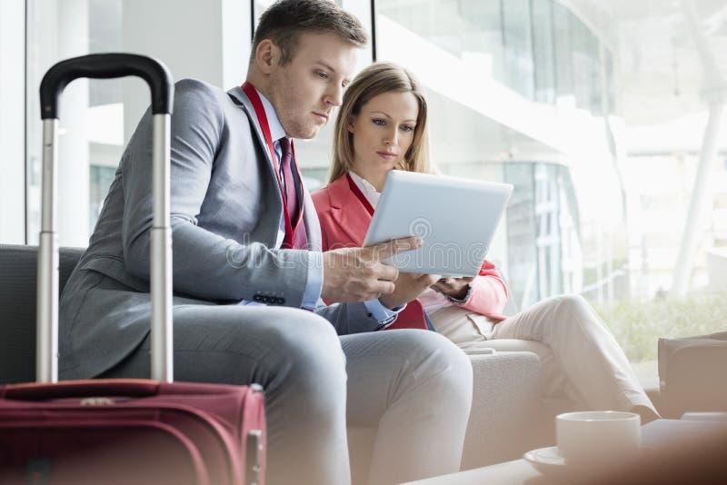 Executivos que usam a tabuleta digital ao sentar-se na entrada no centro de convenções imagem de stock