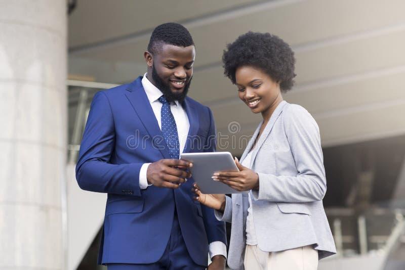 Executivos que usam a tabuleta digital e discutindo o projeto novo fora imagem de stock royalty free