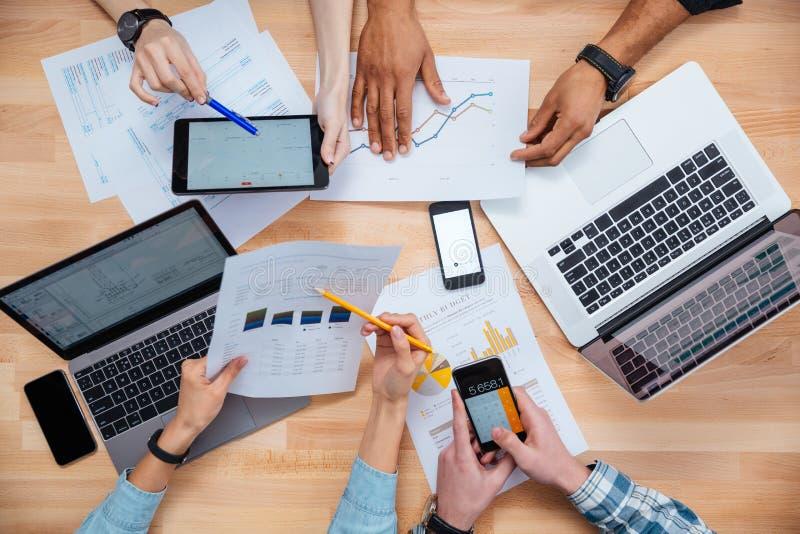 Executivos que usam telefones celulares e portáteis para fazer o relatório fotografia de stock royalty free