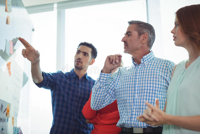 Executivos sérios que discutem sobre o whiteboard fotos de stock