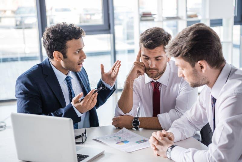 Executivos sérios que sentam-se na tabela e que discutem diagramas no escritório foto de stock royalty free