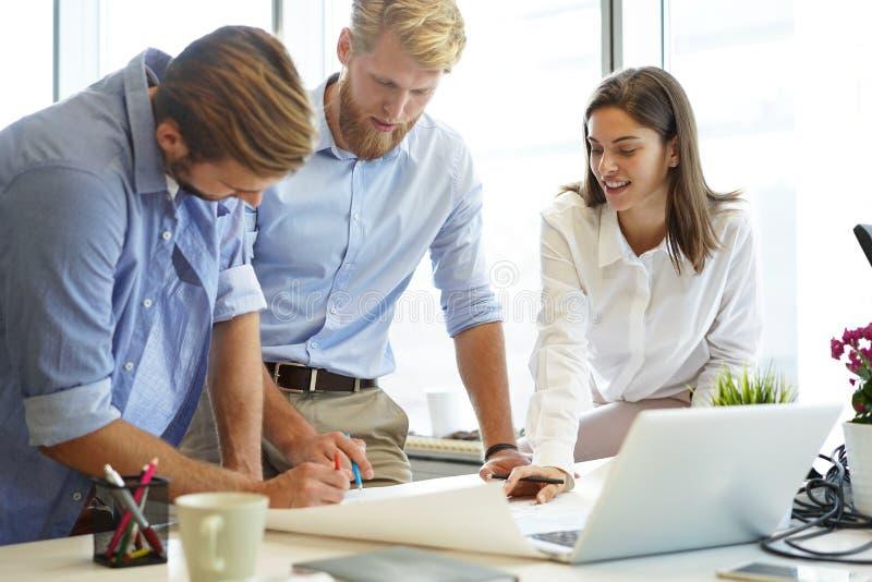 Executivos seguros novos que discutem algo ao olhar o modelo no escritório, equipe da arquitetura imagens de stock royalty free