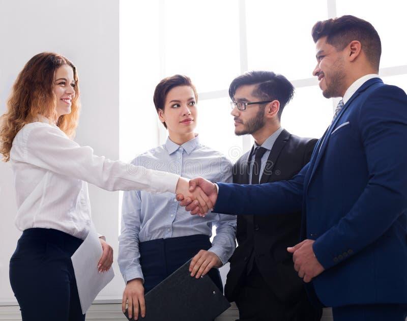 Executivos seguros que agitam as mãos no local de trabalho imagem de stock