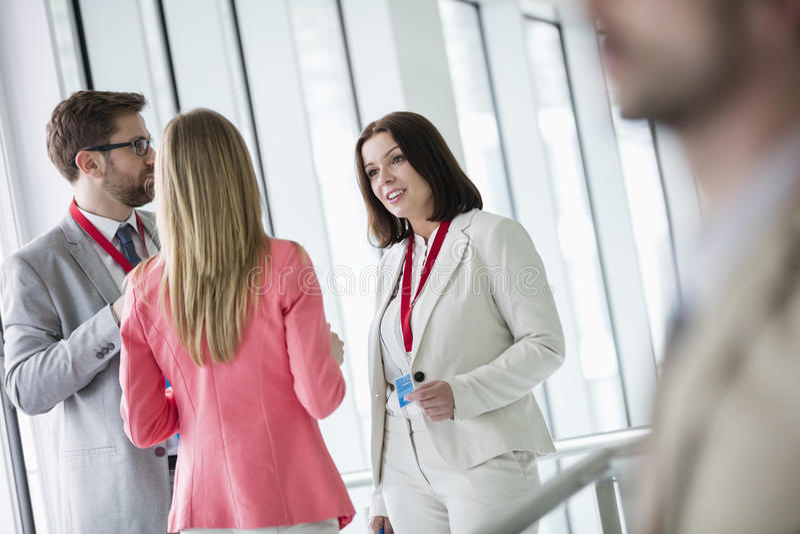 Executivos seguros que discutem no centro de convenções brilhantemente iluminado foto de stock