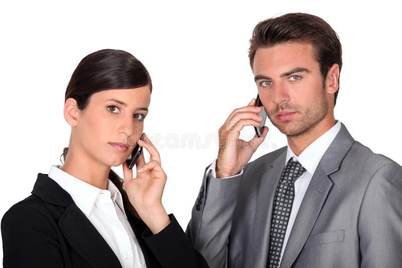 Executivpaare unter Verwendung der Mobiltelefone stockbild