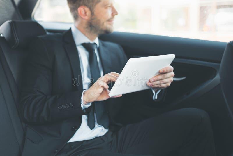 Exekutivgeschäftsmann an der Rückseite des Autos unter Verwendung einer digitalen Tablette stockfotos