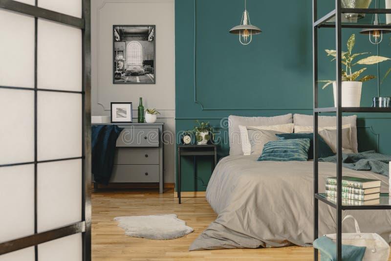 Exemplaarruimte op lege groene muur van modieus slaapkamerbinnenland met warm beddegoed stock afbeelding