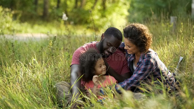 Exemplary couple dedicate their free time to only child, relaxing in summer park. Stock photo royalty free stock photos