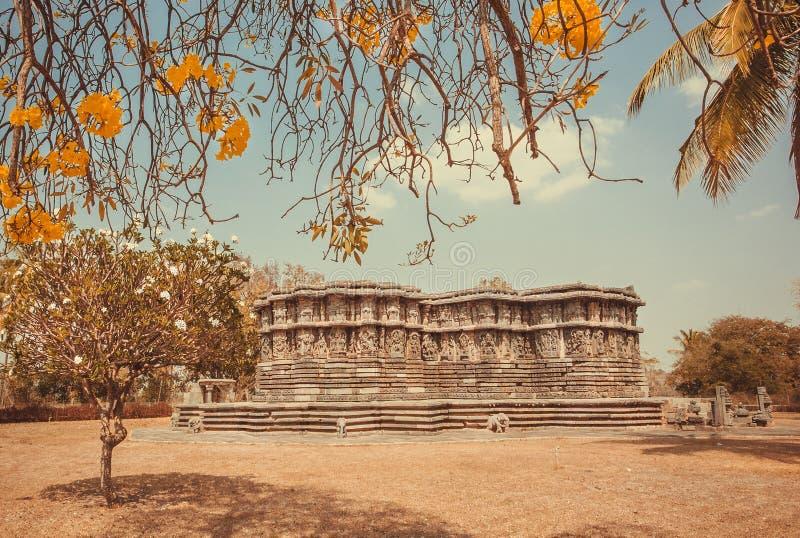 Exemplo da arquitetura histórica na Índia Estacione com árvores, as flores amarelas e o templo do século XII, Índia foto de stock