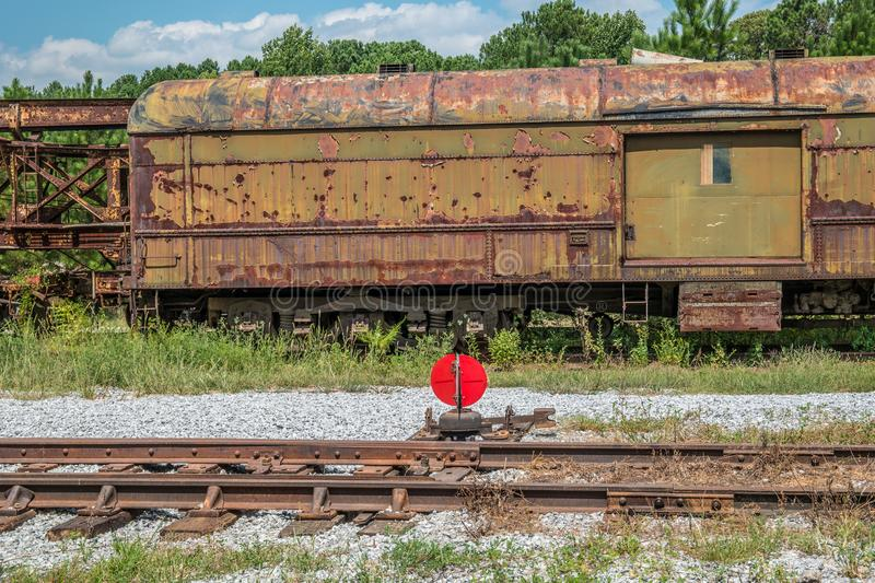 Rusted vintage boxcar abandoned. On exempt train tracks sits an old vintage abandoned railroad boxcar covered in weeds alongside a track switcher on a sunny day royalty free stock images
