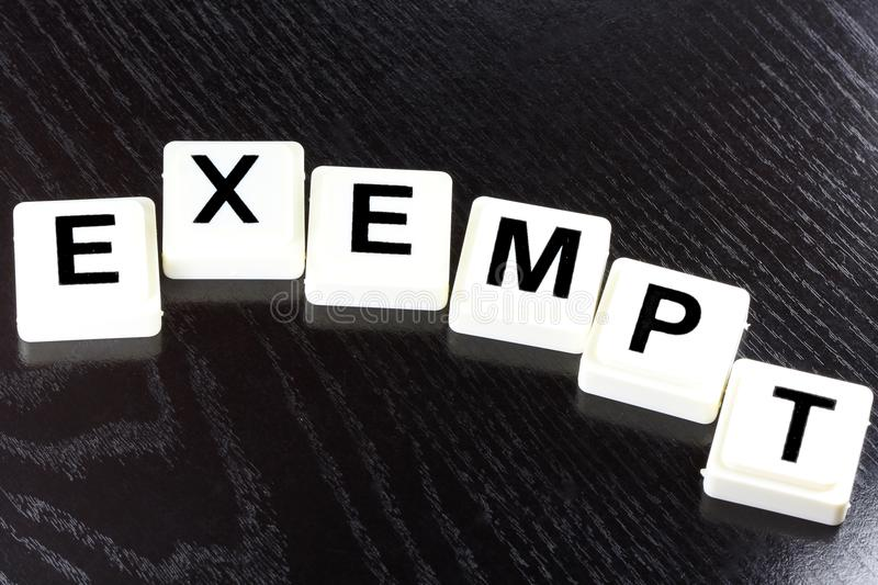 Exempt. The Word Exempt Spelled Out With White Tiles On Black Background - A Term Used For Business, Finance and Tax Concept stock photo