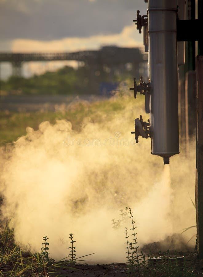 Exerça pressão sobre a tubulação com o fumo que flui do tubo do metal na refinaria de petróleo foto de stock