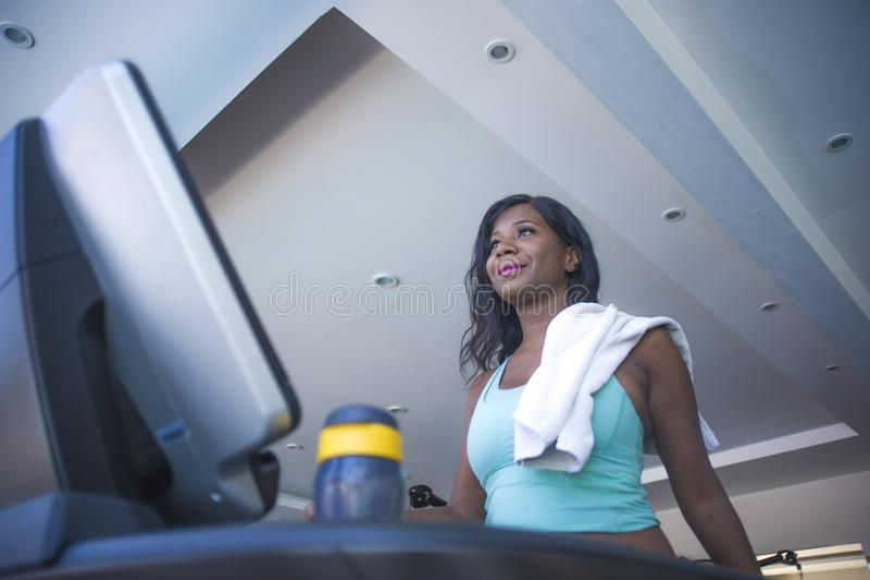 Exercício afro-americano preto atrativo e suado novo do corredor e do passeio da escada rolante do treinamento da mulher no sorri imagem de stock royalty free