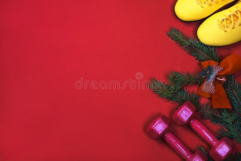 Exercício, aptidão, esporte e Feliz Natal e de ano novo feliz fundo dar certo com pesos, sapatilhas dos amarelos, ramos imagem de stock