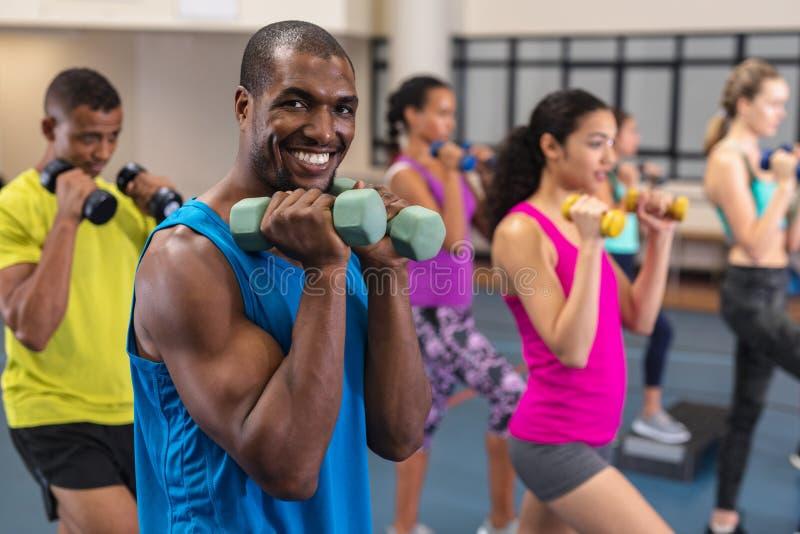 Exercício atlético masculino com pesos no fitness center imagem de stock