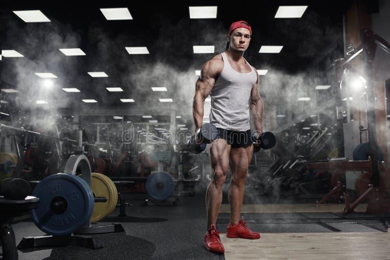 Exercício atlético muscular do modelo do esporte da aptidão do halterofilista no gym fotografia de stock