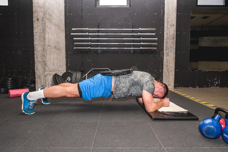 Exercício atrativo e ativo muscular novo da prancha do exercício do homem no gym para a força e acondicionamento com a placa do p imagens de stock royalty free