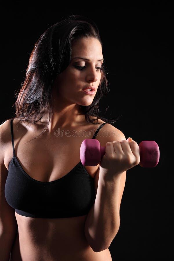 Exercício bonito da onda do bicep da mulher na ginástica foto de stock