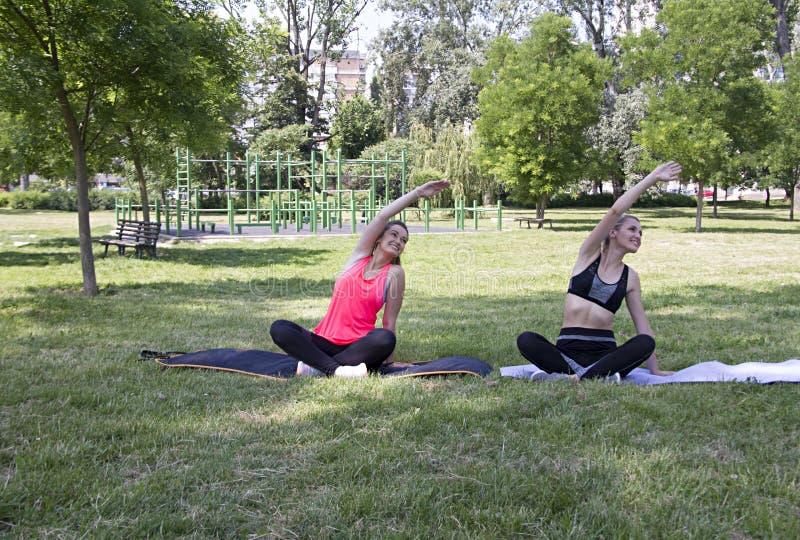 Exercício da aptidão da ioga no parque Esticão dos braços e dos ombros imagens de stock