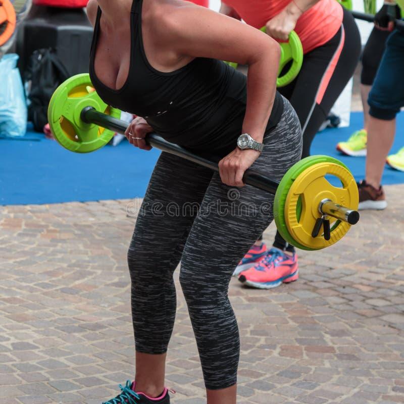 Exercício da aptidão: Menina bonita que usa o Barbell no Gym imagens de stock