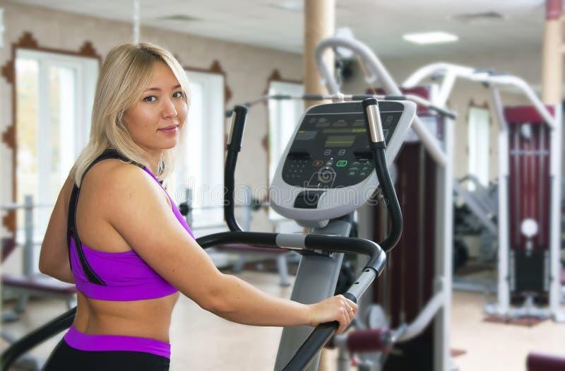 Exercício da aptidão da menina do Gym Menina da aptidão que exercita no equipamento do gym da escada rolante do moonwalker imagens de stock