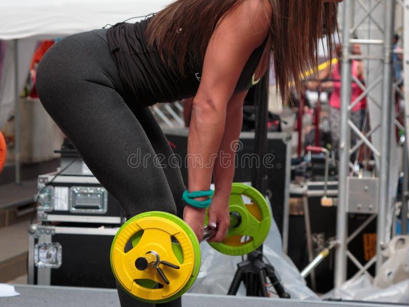 Exercício da aptidão: Moça bonita que usa o Barbell no Gym fotos de stock