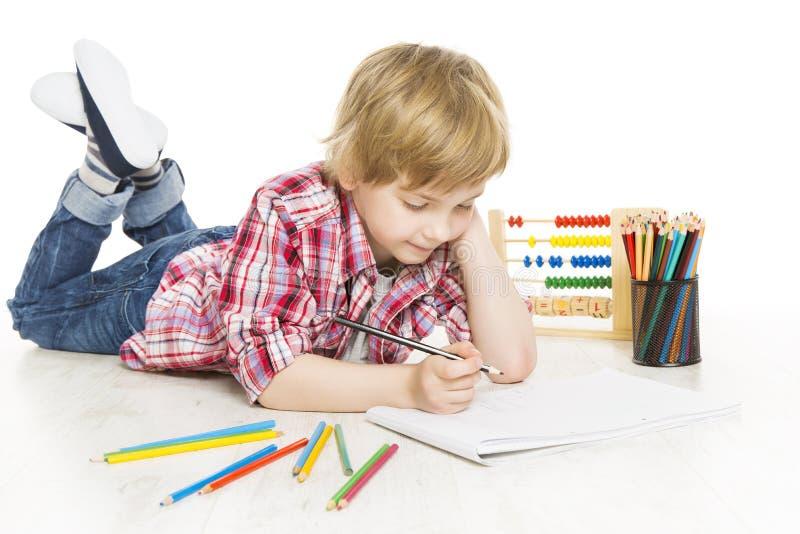 Exercício da escrita do menino de escola no caderno A estudante faz trabalhos de casa imagens de stock royalty free