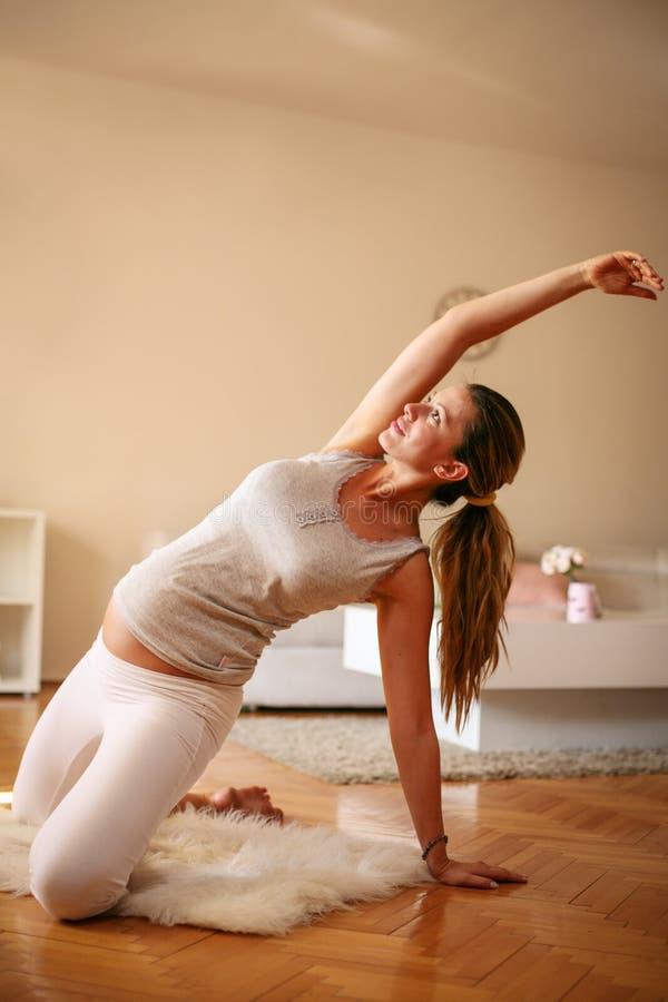 Exercício da jovem mulher em casa fotos de stock