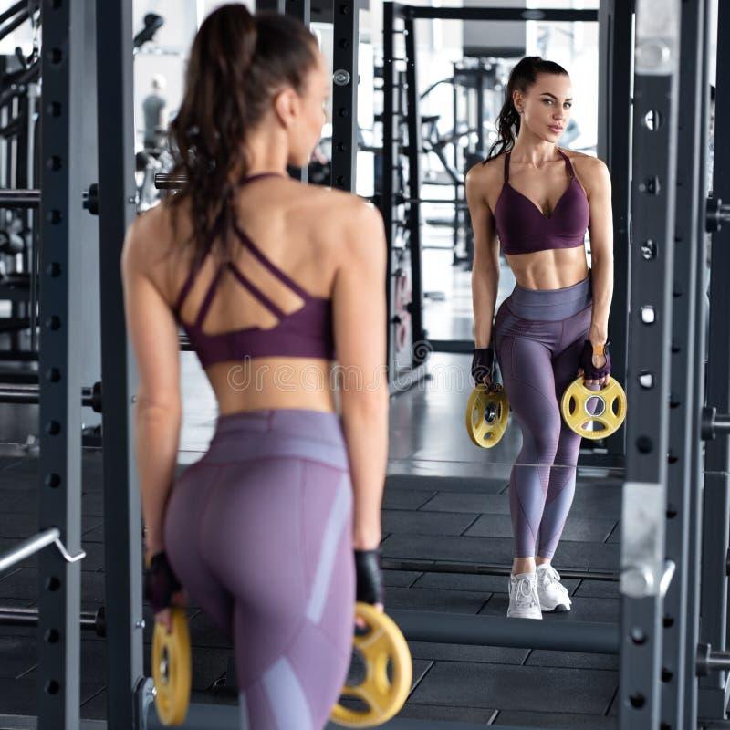 Exercício da mulher da aptidão no gym, menina atlética da cintura magro que faz o exercício Extremidade bonita nas caneleiras imagens de stock royalty free