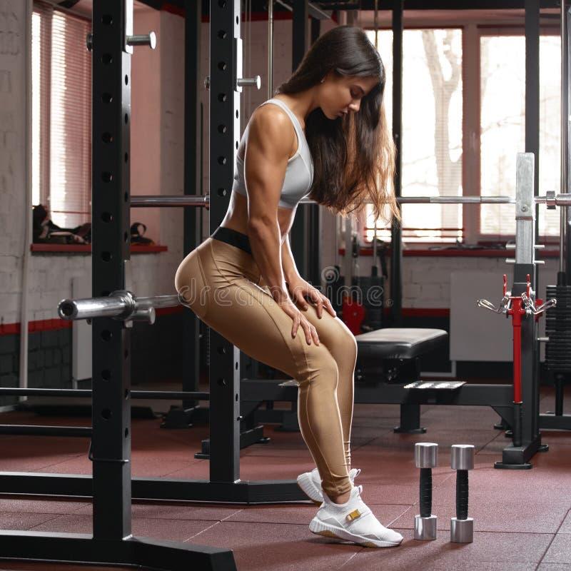 Exercício da mulher da aptidão no gym Menina atlética nova com pesos imagens de stock royalty free