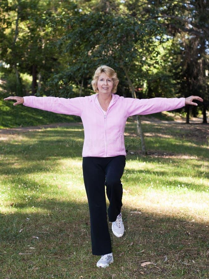 Exercício de equilíbrio da mulher sênior no parque fotos de stock