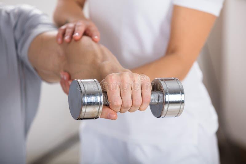 Exercício de Helping Man To do fisioterapeuta foto de stock