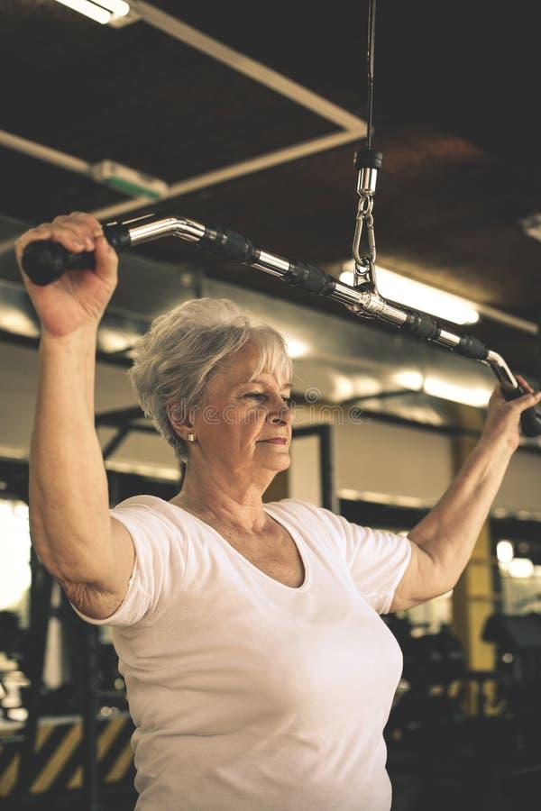 Exercício de trabalho da mulher superior ativa no gym fotos de stock royalty free