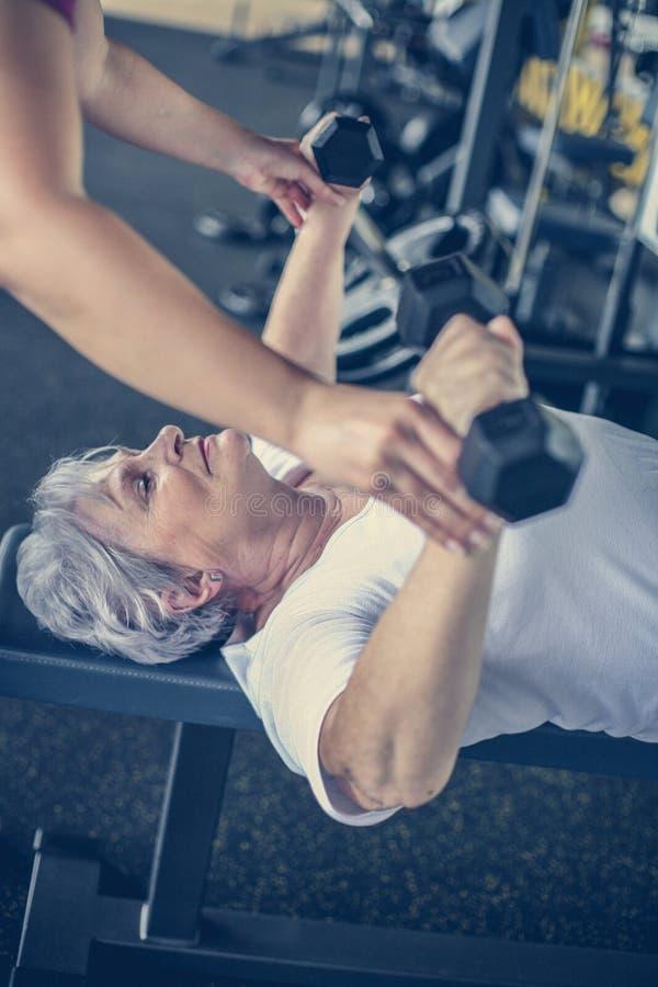 Exercício de trabalho do instrutor com a mulher superior no gym fotos de stock royalty free
