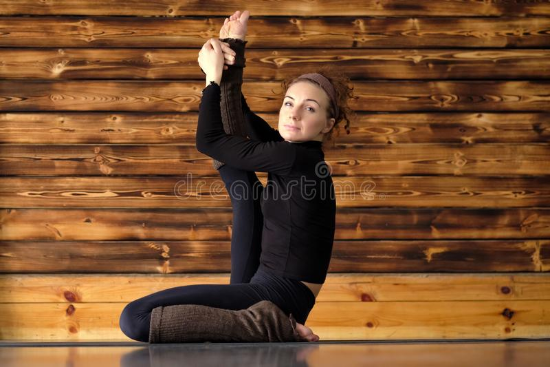 Exercício desportivo da ioga da menina, sentando-se na pose da garça-real, Krounchasana imagens de stock