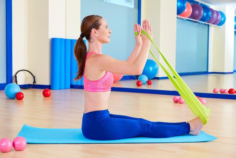 Exercício do elástico do enfileiramento da mulher de Pilates fotografia de stock