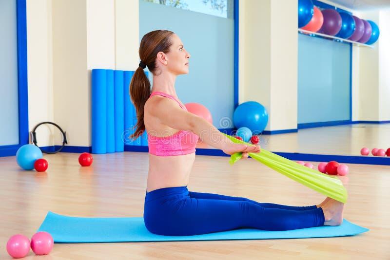 Exercício do elástico do enfileiramento da mulher de Pilates imagens de stock