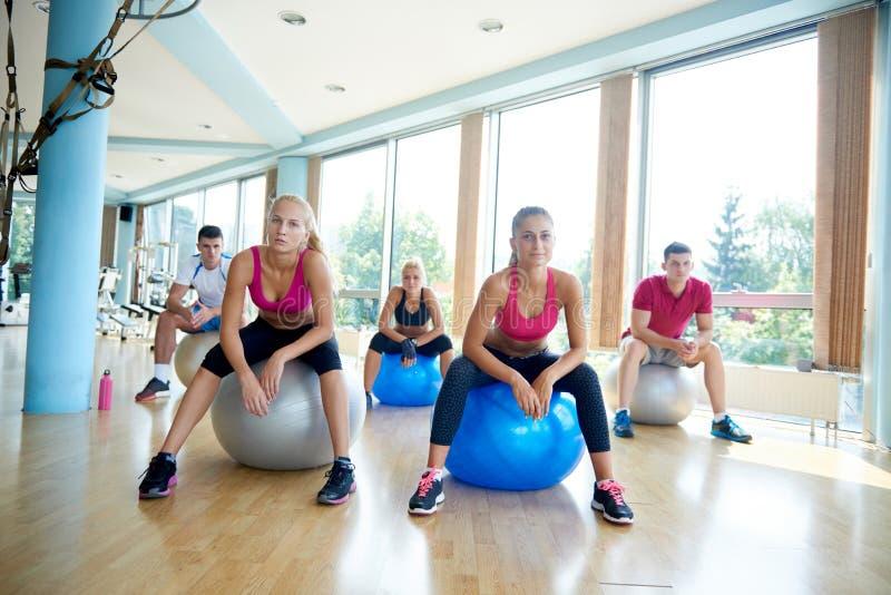 Exercício do grupo de pessoas com as bolas na classe da ioga imagem de stock