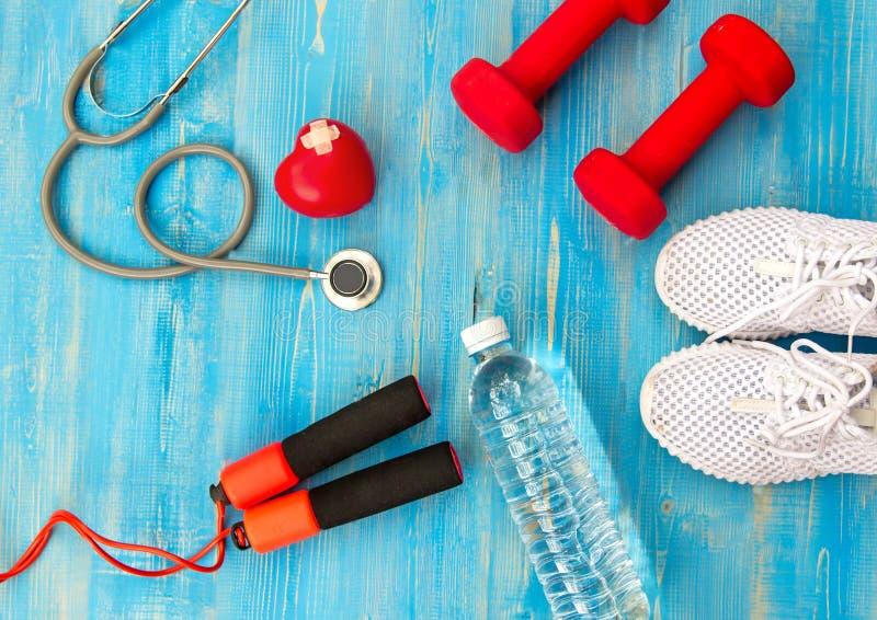 Exercício do gym do equipamento da aptidão e água fresca com coração e estetoscópio médico no fundo azul imagens de stock royalty free