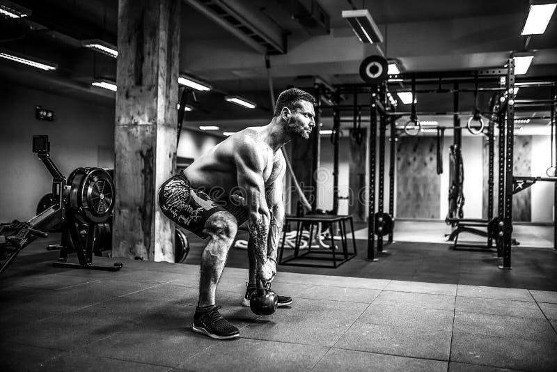 Exercício do homem do exercício do balanço de Kettlebells da aptidão no gym fotografia de stock royalty free